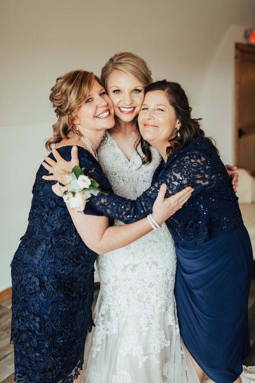 Janelle Elise | Megan + Corey | Furber Farm | Sixpence Events | A Vintage Touch Weddings | moms hug | mother of the bride and mother of the groom in navy lace dresses and hair half up and half down