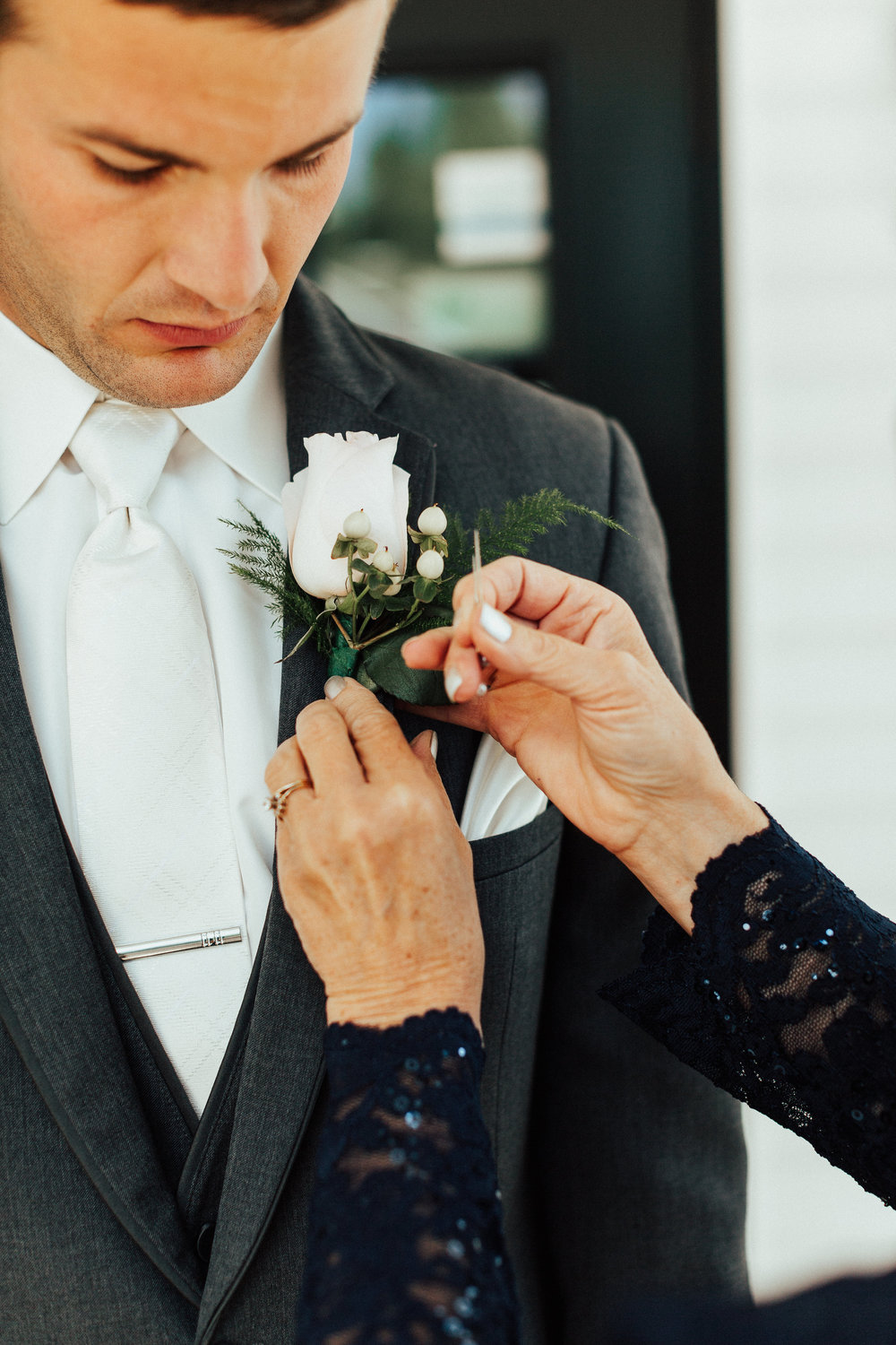 mother of the groom putting on sons bouttonniere | white rose with white hypericum berries and white tie with vest and grey suit | Janelle Elise | Megan + Corey | Furber Farm | Sixpence Events | A Vintage Touch Weddings61.jpg