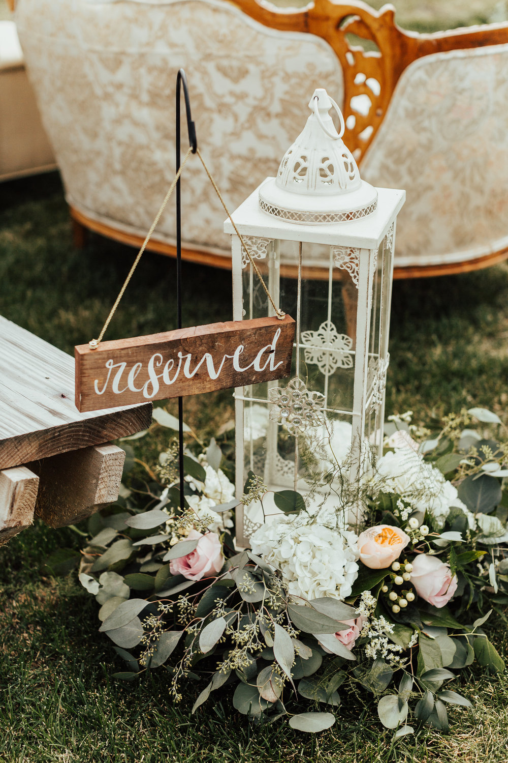 reserved sign with white lantern and floral wreath | vintage couches for first row of family | Janelle Elise | Megan + Corey | Furber Farm | Sixpence Events | A Vintage Touch Weddings100.jpg