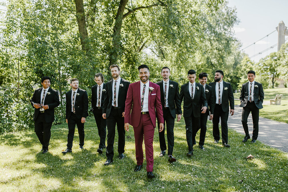 groomsmen with floral tie and black suits | groom in a red suit | Aaron T Photography | Nicolett Island | Sixpence Events and Planning day of coordinating and wedding blog