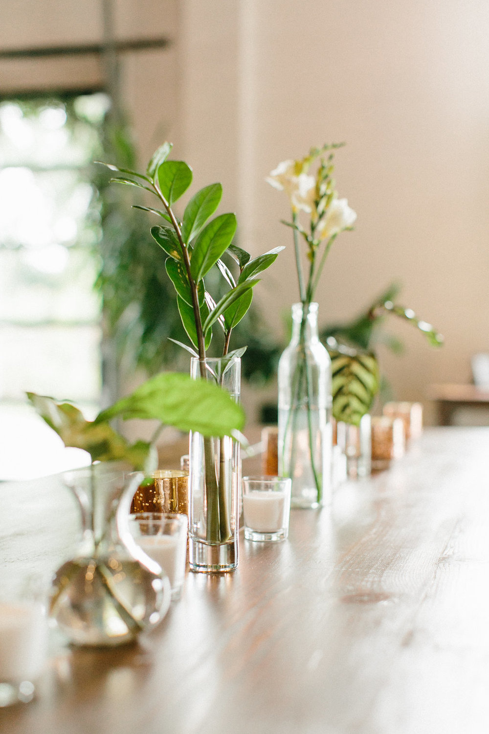 Carly Milbrath Photography | Justin and Jacob | PAIKKA Minnesota Wedding Venue | Same sex wedding with two grooms | bud vases with greenery on harvest table with mercury votives