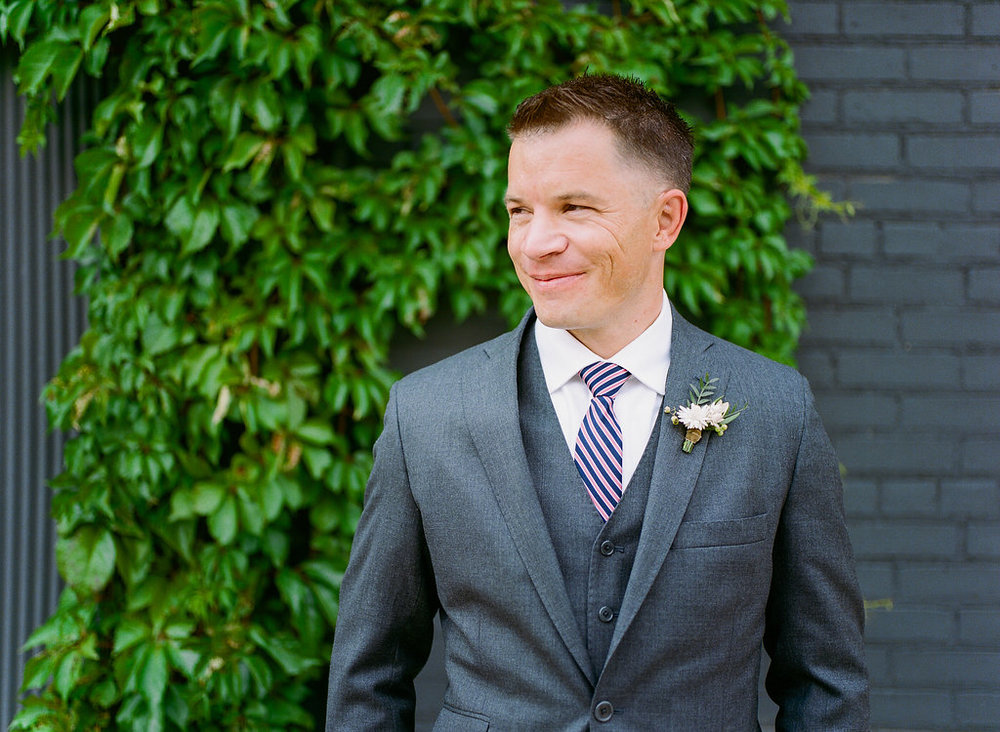 Carly Milbrath Photography | Justin and Jacob | PAIKKA Minnesota Wedding Venue | Same sex wedding with two grooms | groom in front of green vine wall with grey brick backdrop