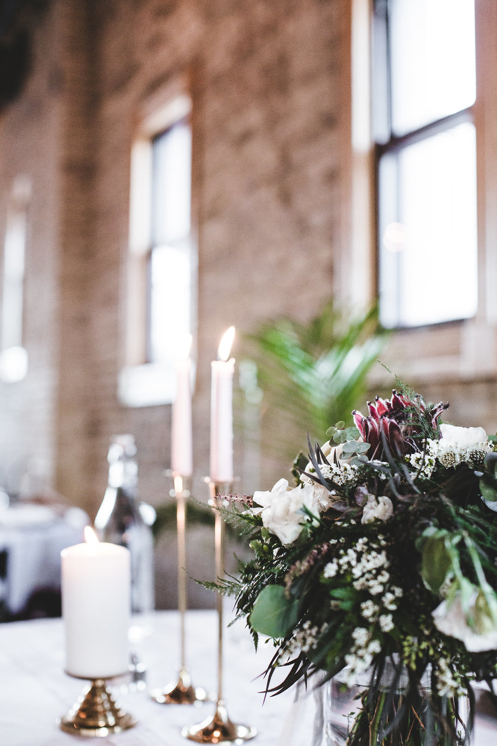 sweetheart table at Day Block Brewery | tapered candles , pale pink | lace runner | Aaron Rice Photo | Sixpence Events day of coordinating