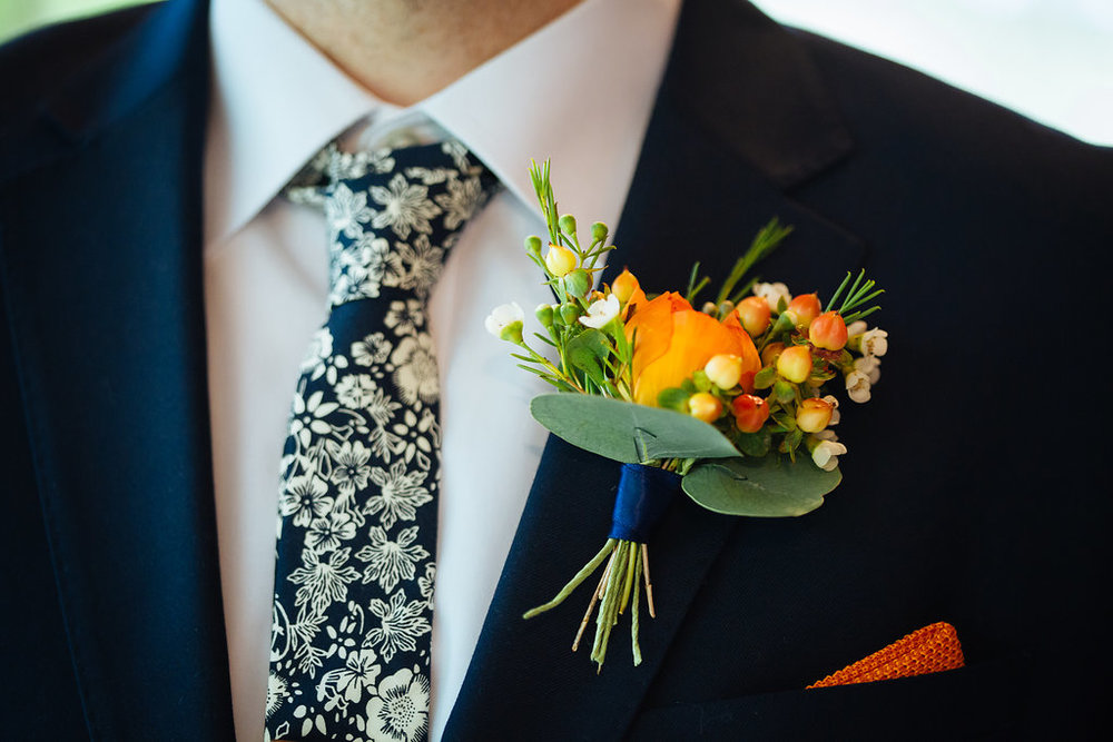 Julia + Johanna | Alyssa Lee Photography | Camrose Hill Flower Studio | bride in navy custom suit with white on blue floral tie | orange pocket square | orange boutonniere with wax flowers, hypericum berries and silver dollar eucalyptus | Sixpence Events and Planning day of coordinating