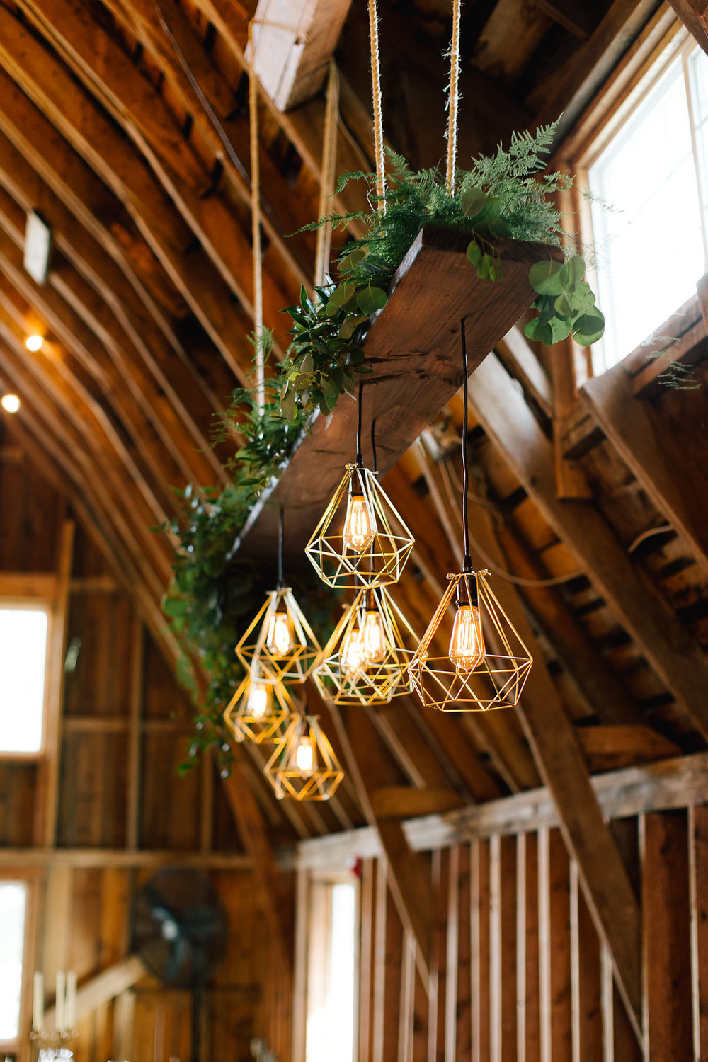 Jade and Seth Bloom Lake Barn wedding | Allison Hopperstad Photography | A Vintage Touch Weddings planning nad design | Day of Coordinating by Sixpence Events | chandelier bar with greenery