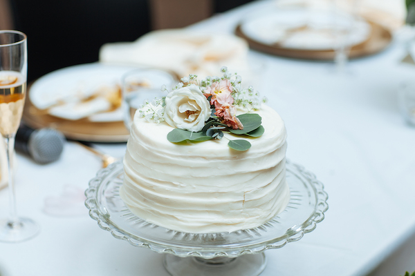 Hailey and Hunter | Alyssa Lee Photography | Sixpence Events & Planning |  one tiered cake with flowers on top and a clear cake stand glass