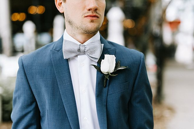 Lydia + Michael Sixpence Events day of coordinating client | Loring Social | Kate Becker Photography | Mann Frau Videography | Minted wedding stationery | groom with white rose boutonniere and gray bowtie in a blue suit and face stubble