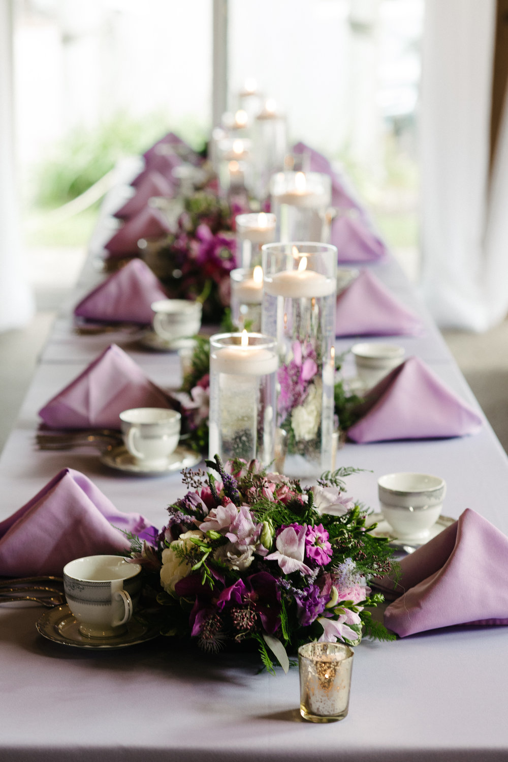 lavender table linen with matching napkins, hurricane vase floating candles |  Dillinger Studios Minneapolis Photographer | Mexican American fusion wedding | Sixpence Events & Planning Minnesota wedding planner .jpg