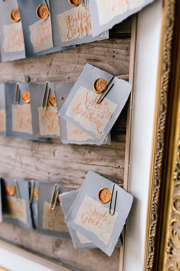 custom wedding guest seating chart with paper clips and a frame, hand calligraphy in copper and a wax seal by A Vintage Touch weddings | Day of coordinating by Sixpence Events | photo by Allison Hopperstad