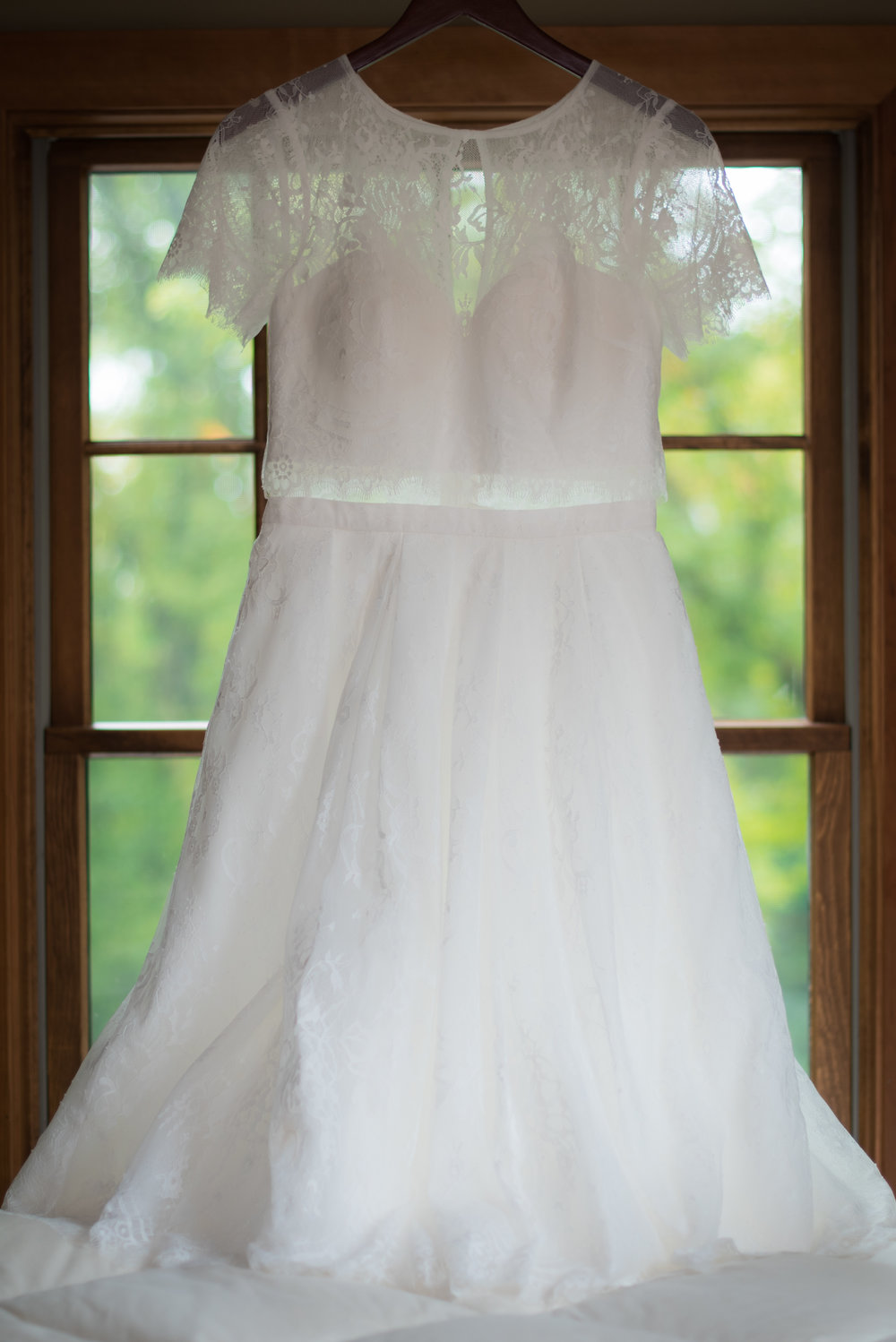 two piece wedding dress hanging in the window // Backyard Wedding in Northfield, MN :: Elliot Malcom Photography :: Megan + Andrew :: Apres Tent Rental :: GastroTruck Catering :: Sixpence Events & Planning .jpg