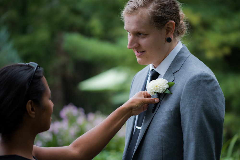 Boutonniere pinning on groom in grey suite with low bun and black tie // Backyard Wedding in Northfield, MN :: Elliot Malcom Photography :: Megan + Andrew :: Apres Tent Rental :: GastroTruck Catering :: Sixpence Events & Planning .jpg