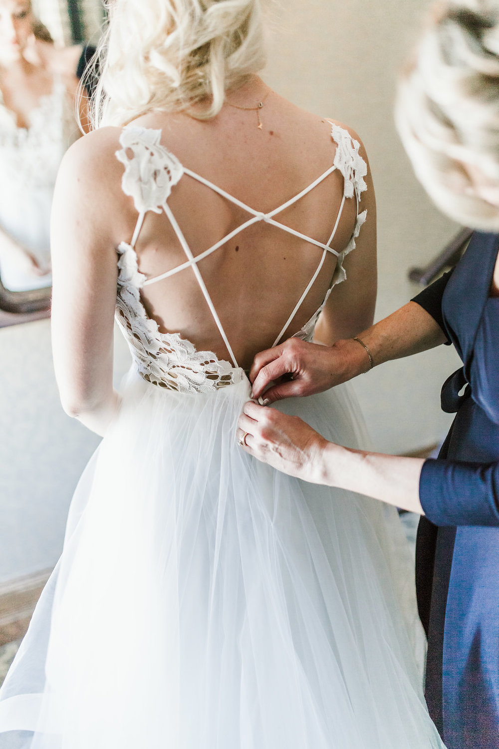 Hayley Paige wedding dress with criss cross strappy back | Aaron T Photography | blonde bride | tulle skirt | mom helping bride into her dress
