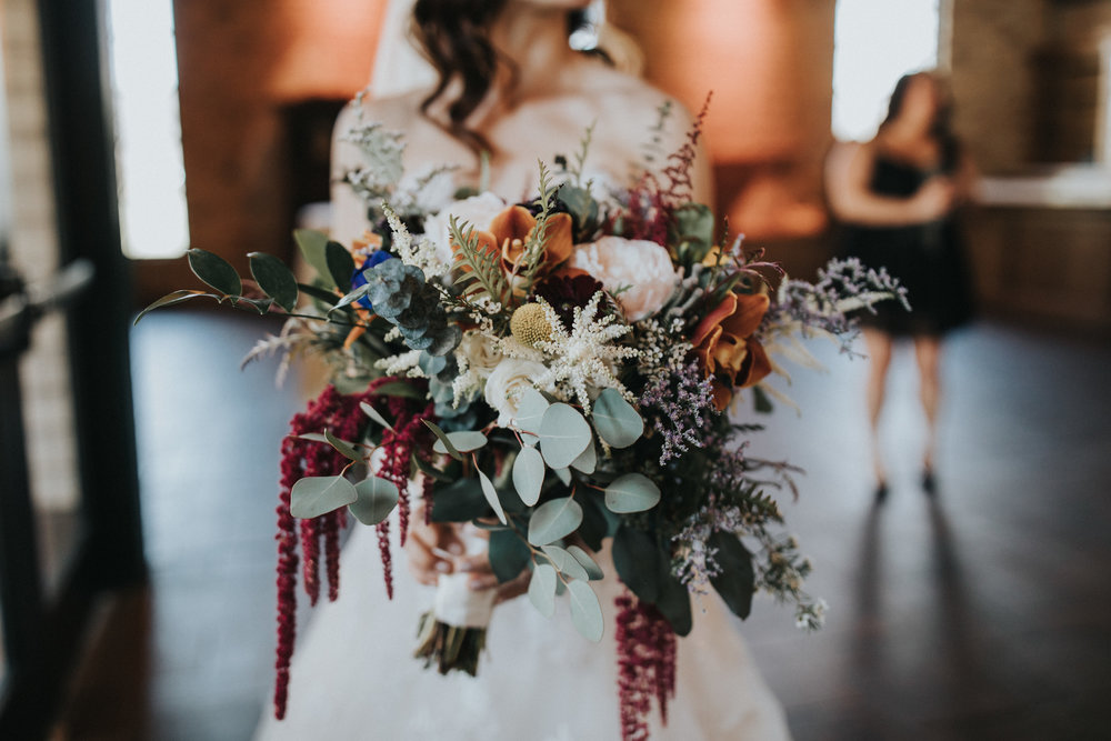 bridal bouquet with orange orchids, astilbe, button mums, eucalyptus, silver dollar eucalyptus, amaranthus | Russell Heeter Photography :: Minneapolis wedding planner Sixpence Events :: Nicollet Island Pavilion :: april wedding in Minnesota.jpg
