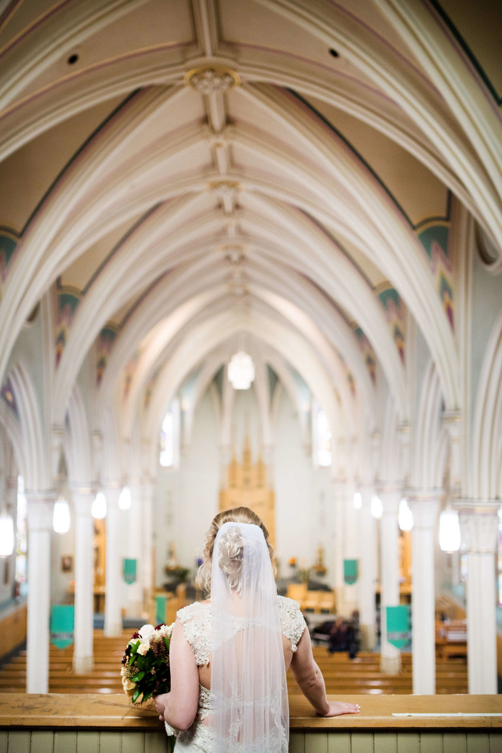 bride looking out at the congregation with church ceiling details | Minnesota wedding photographer Studio KH wedding dress details | wedding blog | Sixpence Events 70 Ways to Photograph Your Wedding Dress.jpg