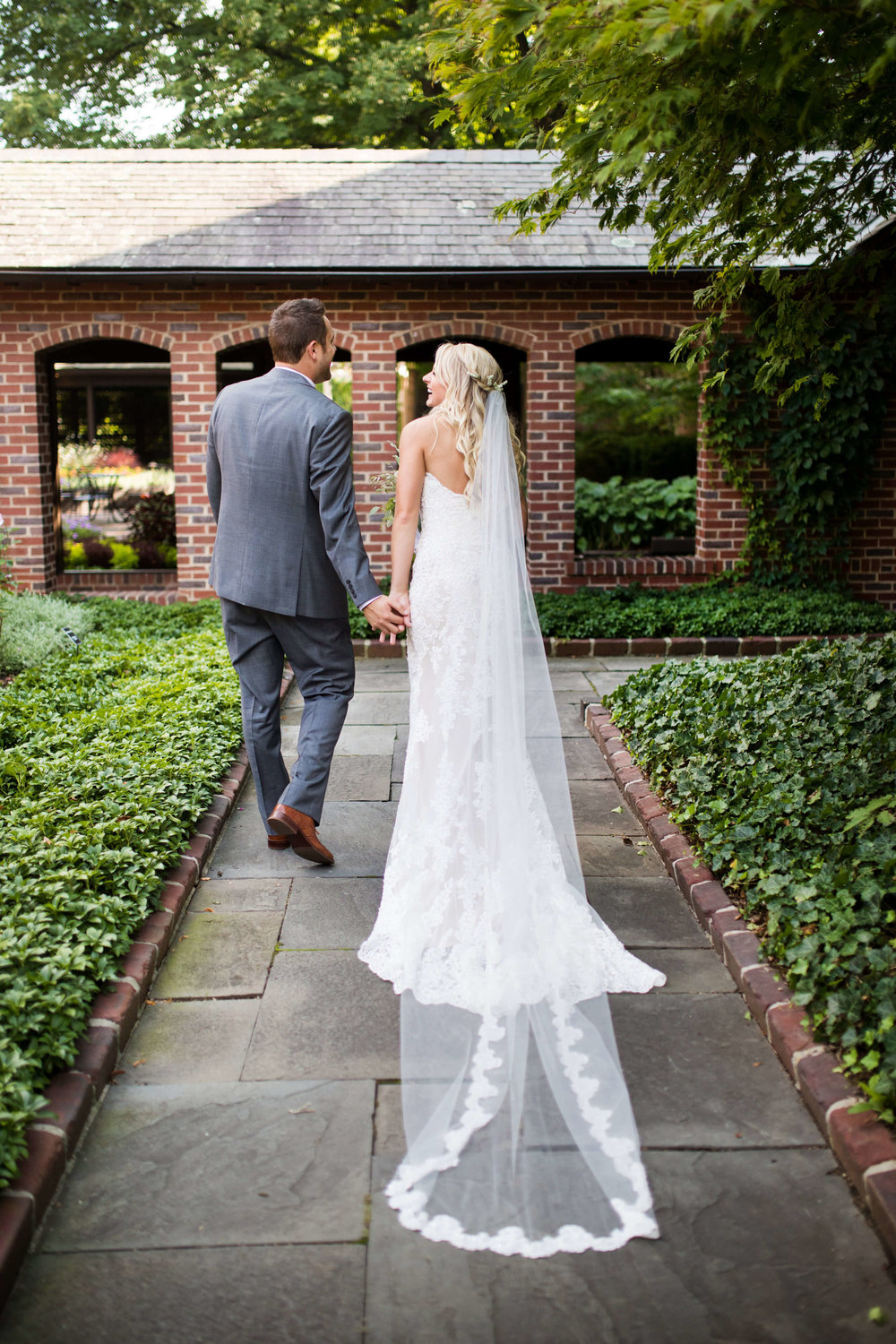 long veil view from the back | bride and groom walking in brick and green garden with ground cover | bride with hair half down | Studio KH | 70 ways to photograph your wedding dress | Sixpence Events & Planning