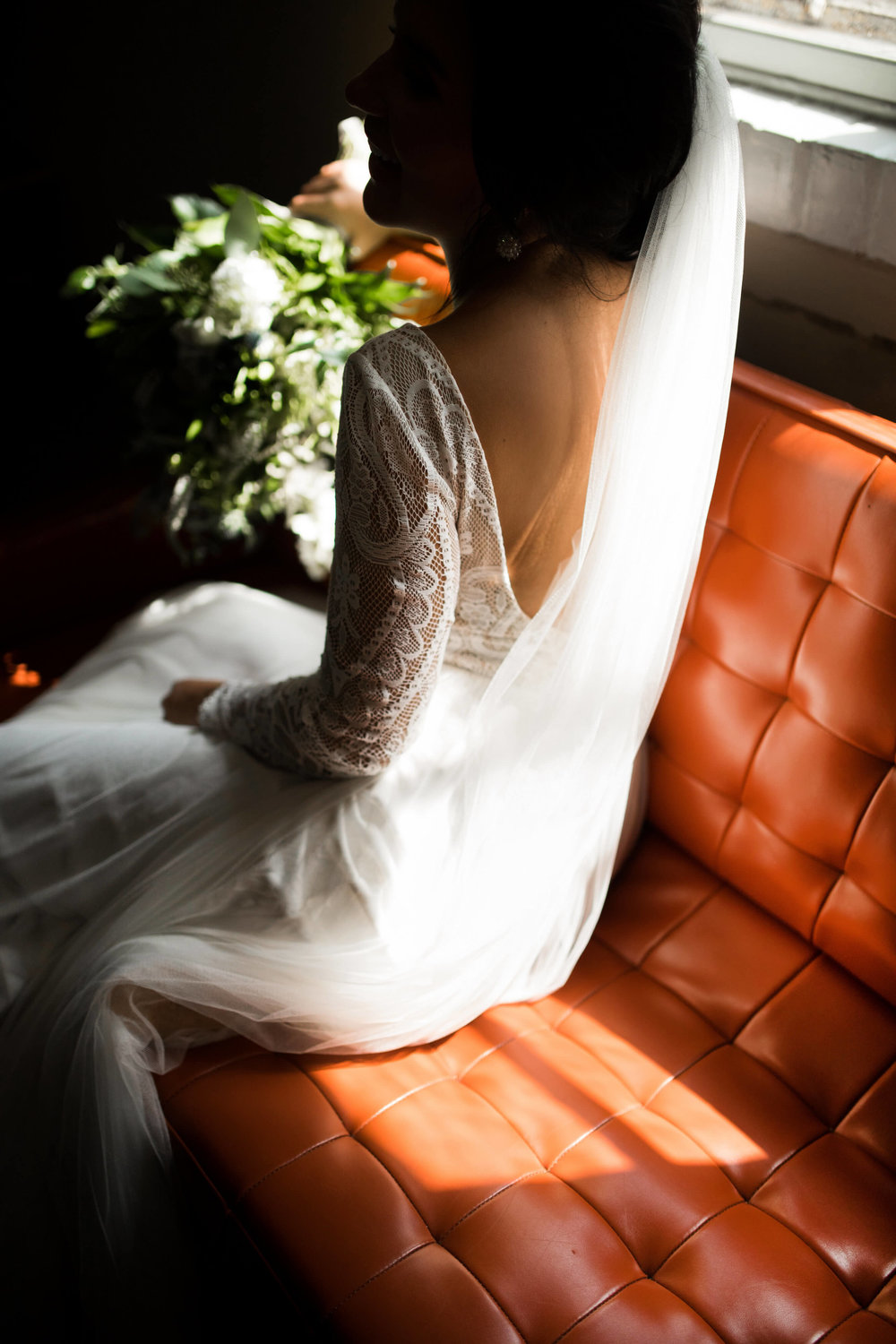 Studio KH wedding photographer | Sixpence Events and Planning, free wedding blog, free wedding help, free wedding advice | bride sitting on leather couch with lace detail sleeves and a scoop back