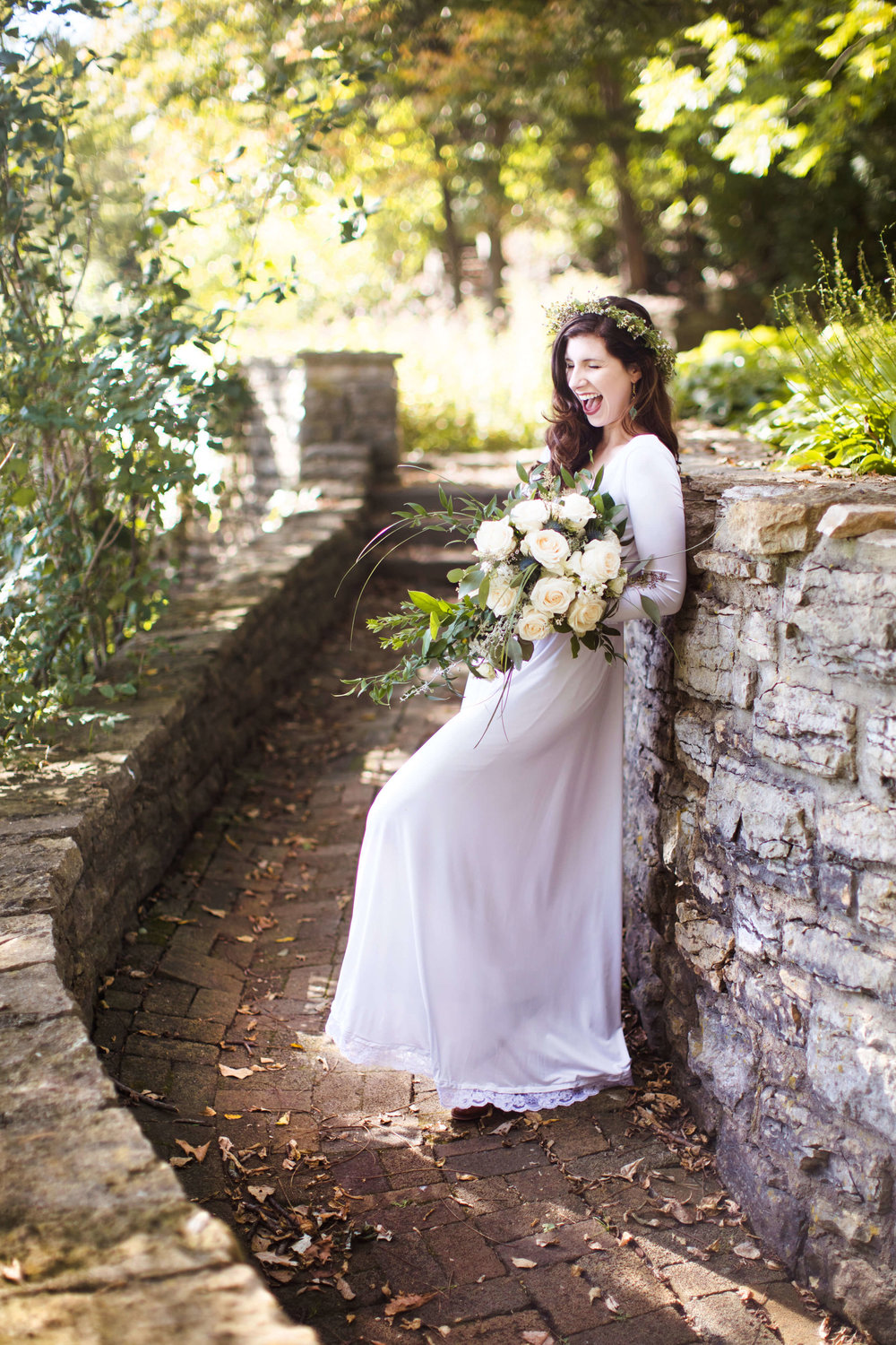 Studio KH wedding photographer | Sixpence Events and Planning, free wedding blog, free wedding help, free wedding advice | bride on the stone wall with floral crown and silk gown with lace edging | large bouquet with white and greens