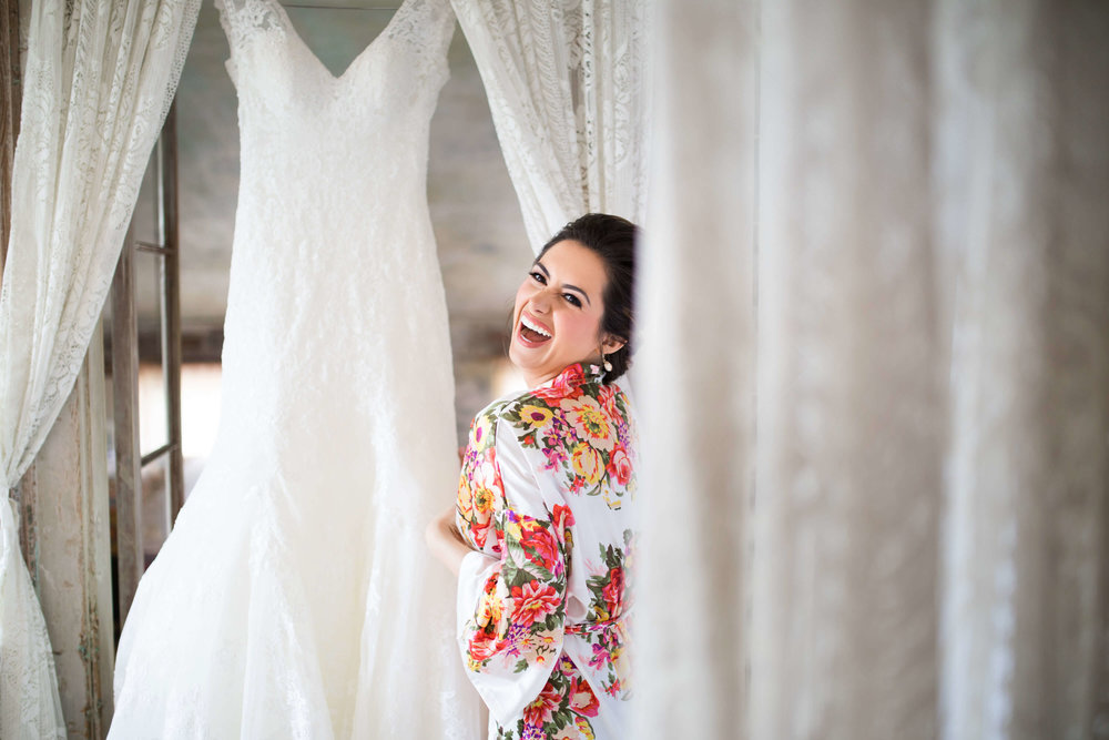 floral print getting ready robe | bride looking at her dress | Minnesota wedding photographer Studio KH wedding dress details | wedding blog | Sixpence Events 70 Ways to Photograph Your Wedding Dress