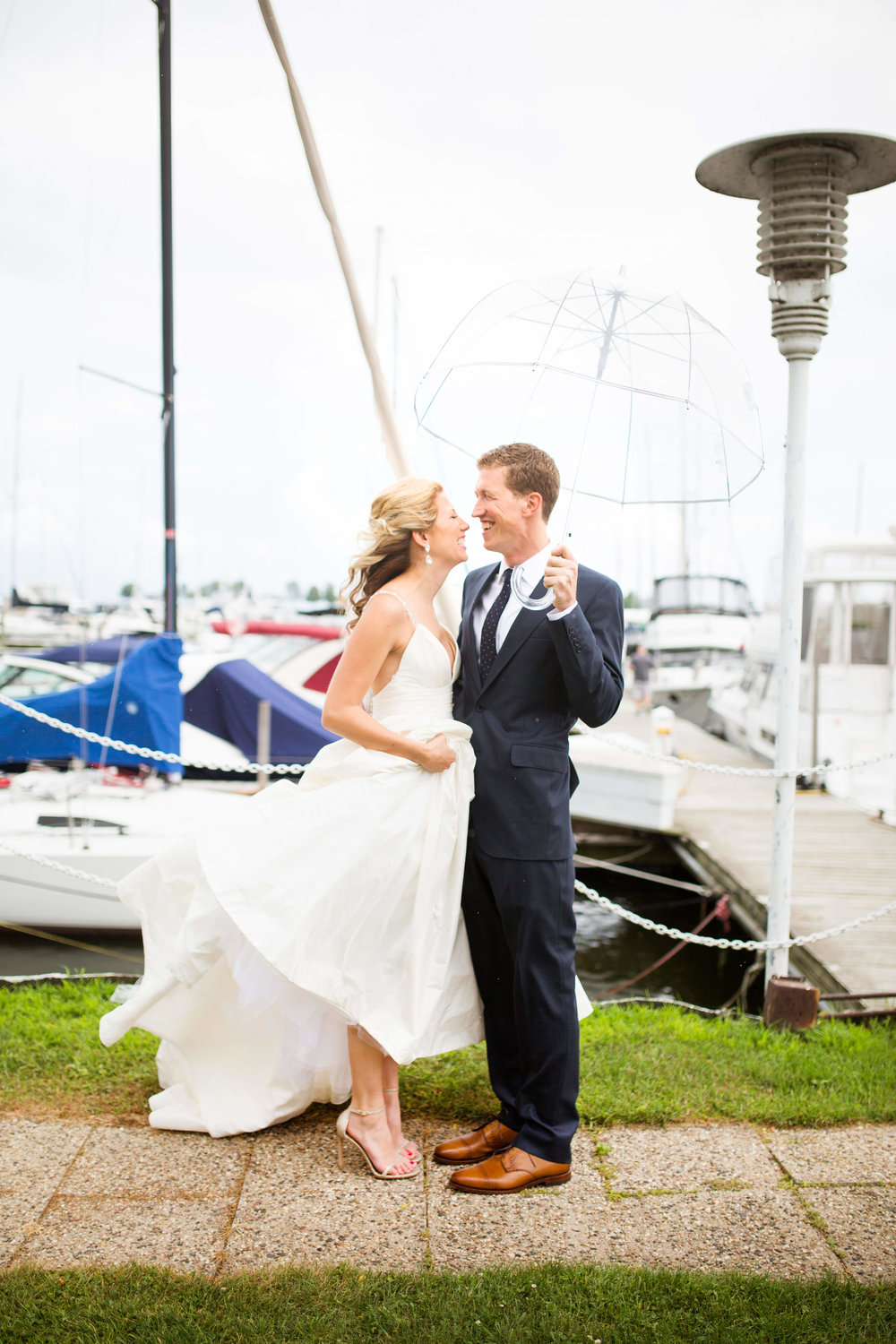 bride and groom at the marina wind swept with clear umbrella | Minnesota wedding photographer Studio KH wedding dress details | wedding blog | Sixpence Events 70 Ways to Photograph Your Wedding Dress.jpg