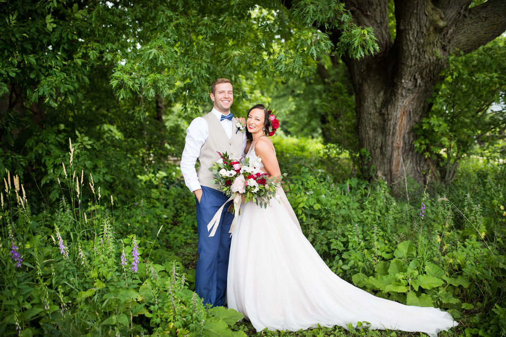 bride and groom in the forest | groom in taupe vest with blue bowtie | bride with large bouquet | Minnesota wedding photographer Studio KH wedding dress details | wedding blog | Sixpence Events 70 Ways to Photograph Your Wedding Dress.jpg