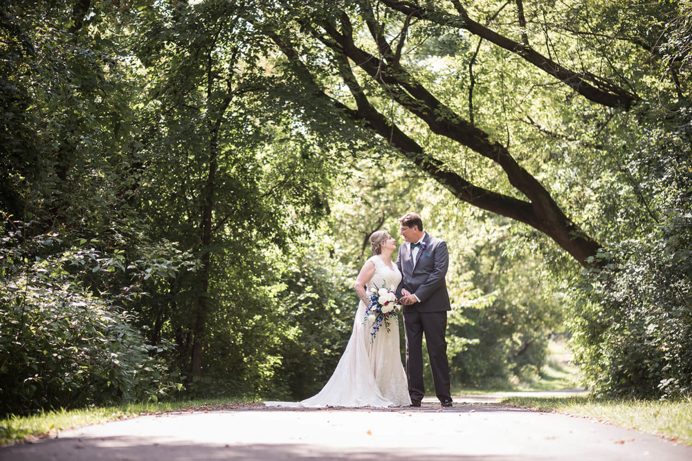 K Solberg Photography | Elm Creek Chalet | Minneapolis day of coordinator Sixpence Events | bride and groom in the road