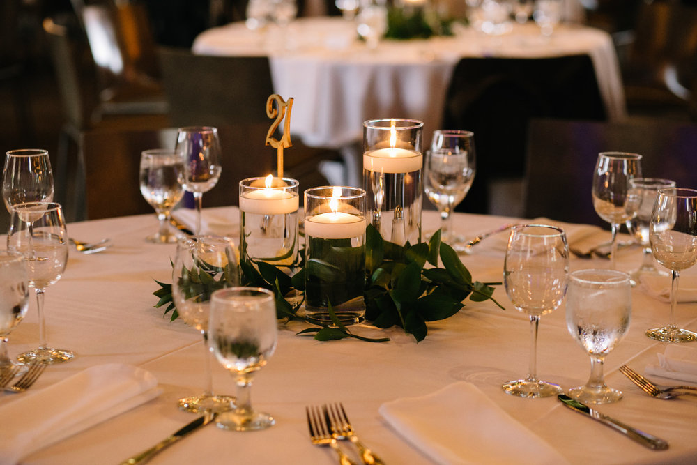 gold die cut table number, floating candles, italian ruscus, white napkin with white table cloth, Whims and Joy Minneapolis photographer :: Sixpence Events & Planning Minnesota wedding planner :: Nicollet Island Pavilion.jpg