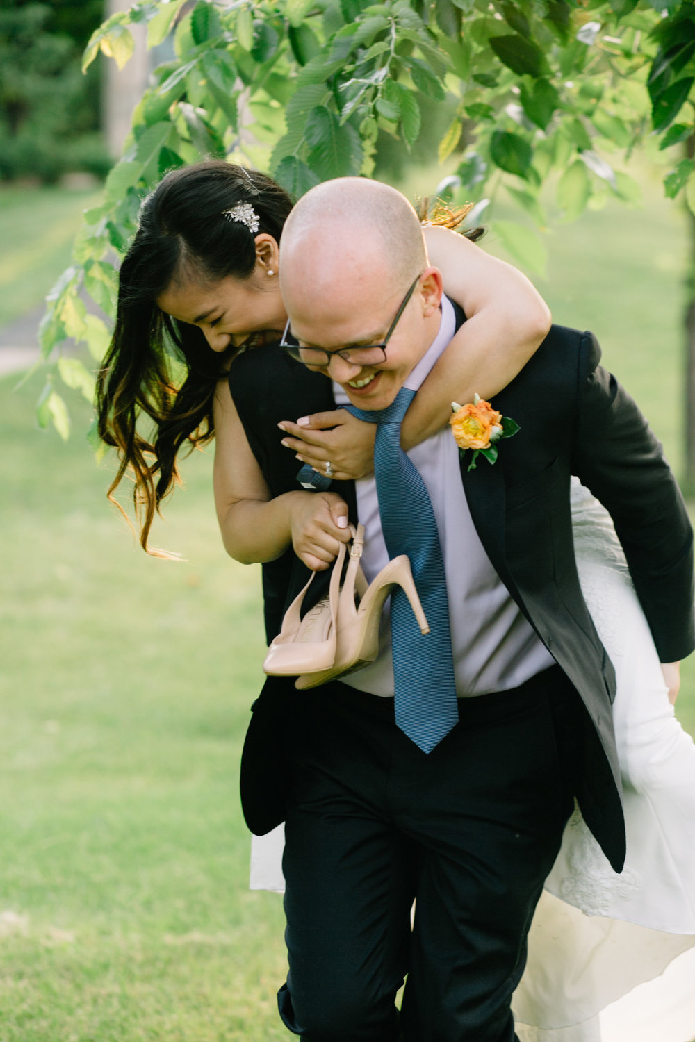 piggy back ride, shoes off, happy bride and groom, Whims and Joy Minneapolis photographer :: Sixpence Events & Planning Minnesota wedding planner :: Nicollet Island Pavilion.jpg