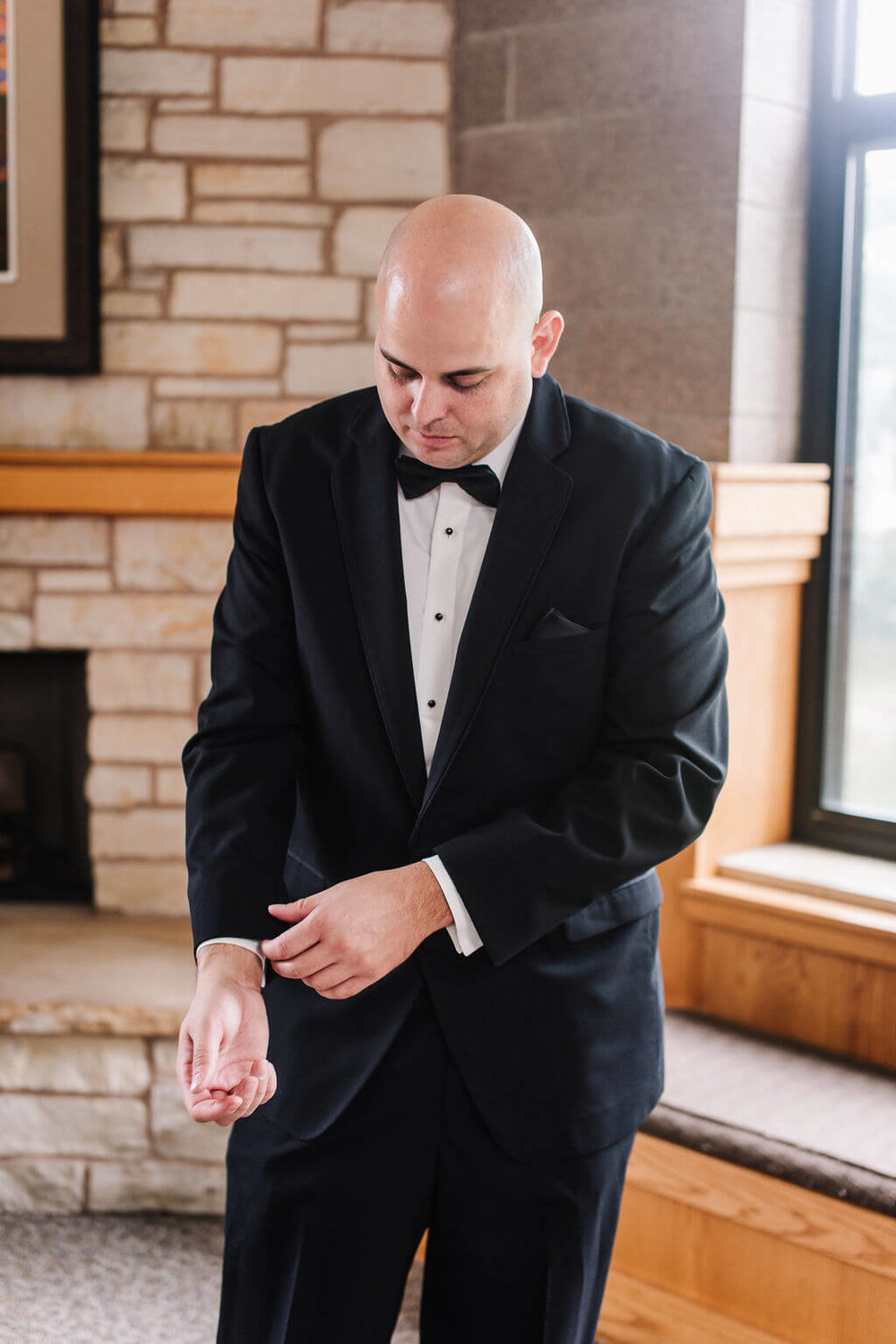 Laura Haya Photography | Sixpence Events Day of Coordinating | Bunker Hills Event Center Minnesota | groom in black tux with bow tie, bald groom