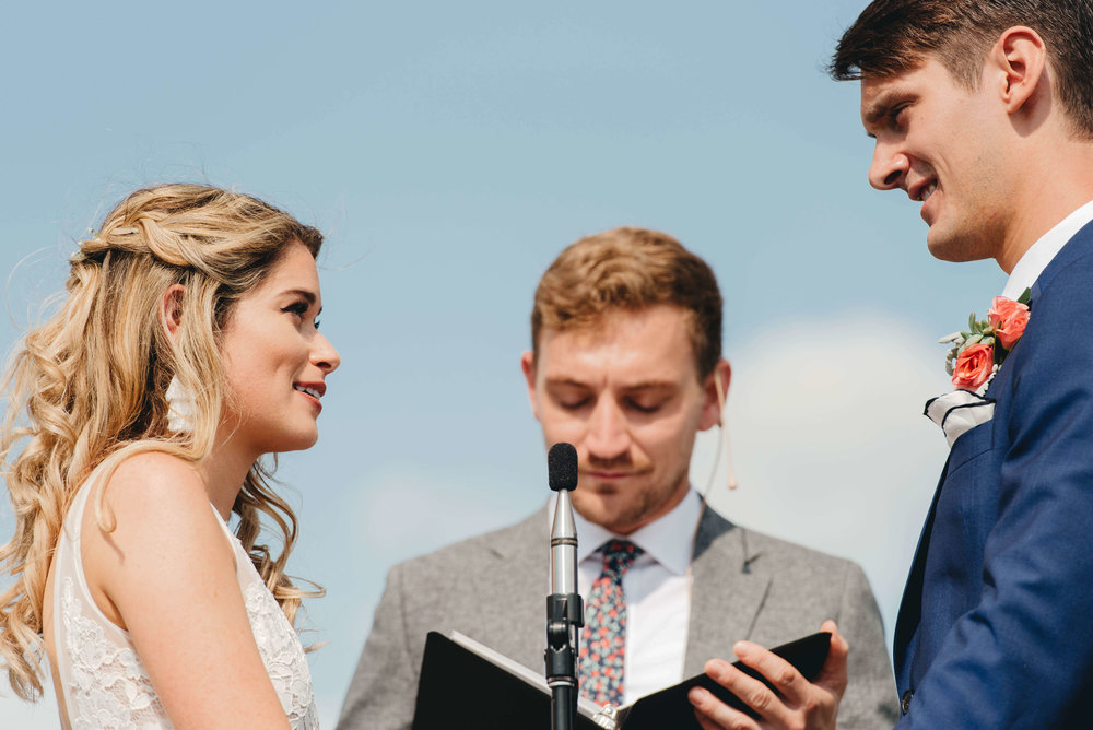 Roy Son Photography | Raspberry Island and Octo Fish bar | Minneapolis wedding planner Sixpence Events | vows under a blue sky | skinny microphone with head set lavalier