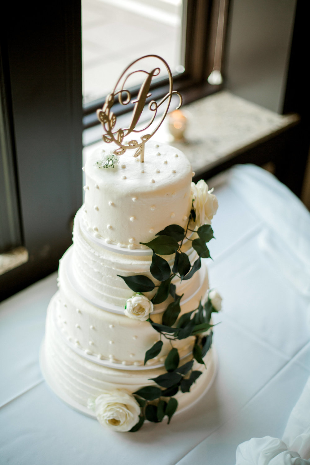 four tiered white cake with greenery and last name initial laser cut cake topper | Lauren Baker Photography | Sixpence Events Blog Post: Must Have Wedding Photography Tips