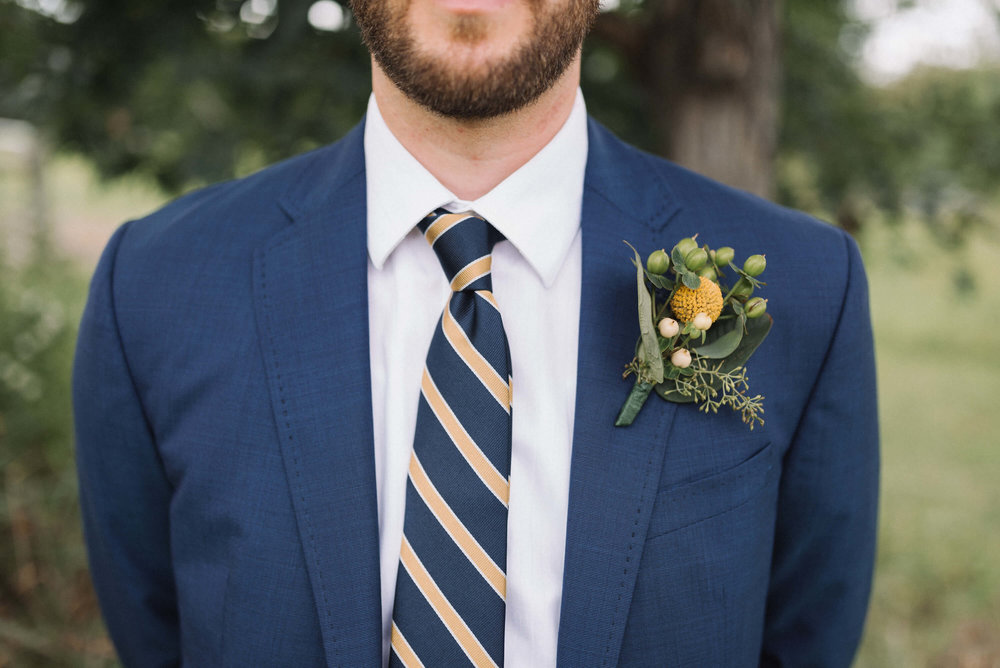 groom in navy with striped yellow tie and billy ball boutonniere | Jonny and Liz Minnesota Wedding Photographers | Sixpence day of coordinating at Gale Woods farm venue near the lake.JPG