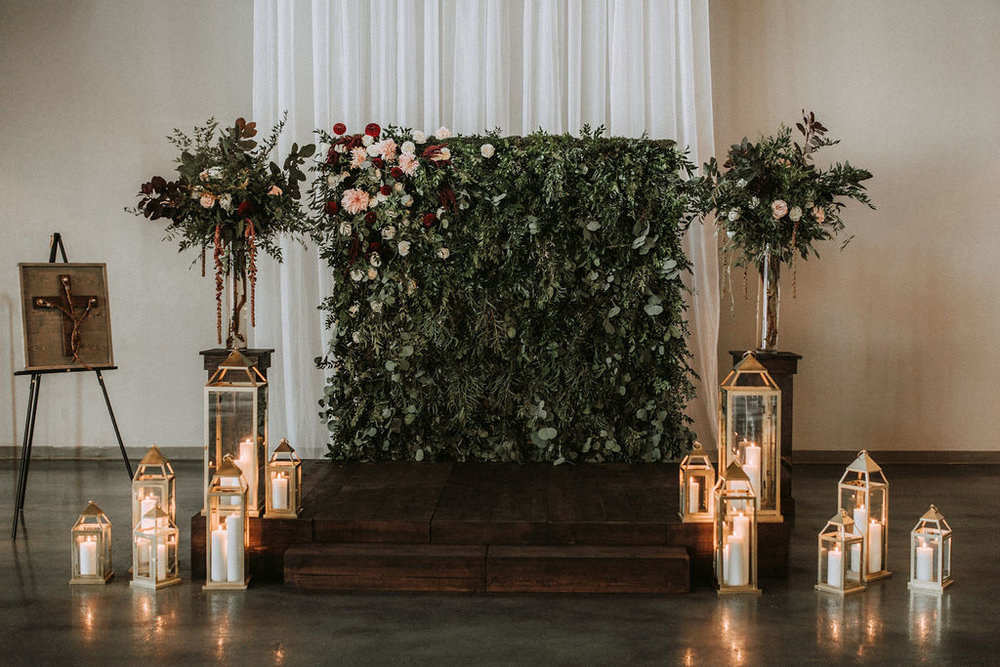 boxwood wall DIY wood stage dark stain and wood pillars with gold lanterns in front of the draped wall | Asher Marie Photography | Minneapolis day of coordinator | Muse wedding downtown.jpg