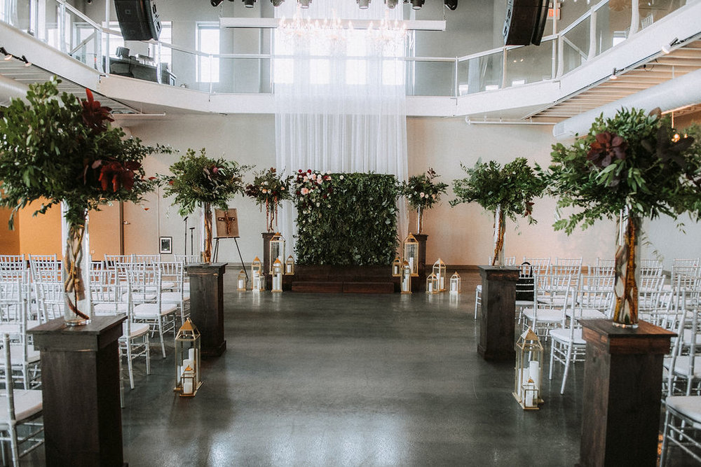 wood pedestals with homemade stage for ceremony and tall pillar floral arrangements | Asher Marie Photography | Minneapolis day of coordinator | Muse wedding downtown.jpg