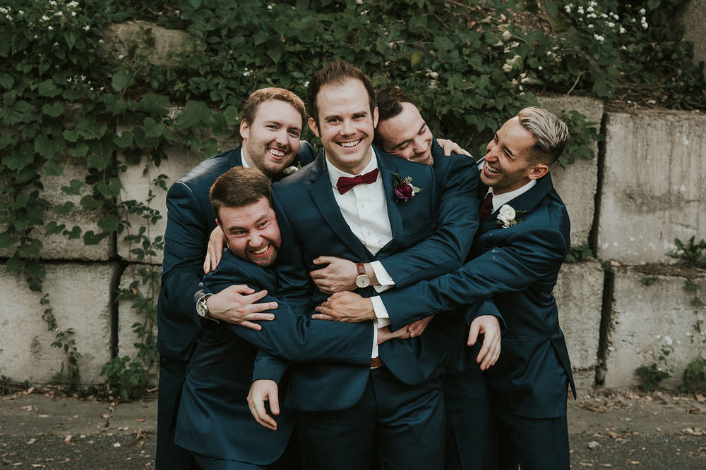 groomsmen hugging groom in navy with burgundy | Asher Marie Photography | Minneapolis day of coordinator | Muse wedding downtown.jpg
