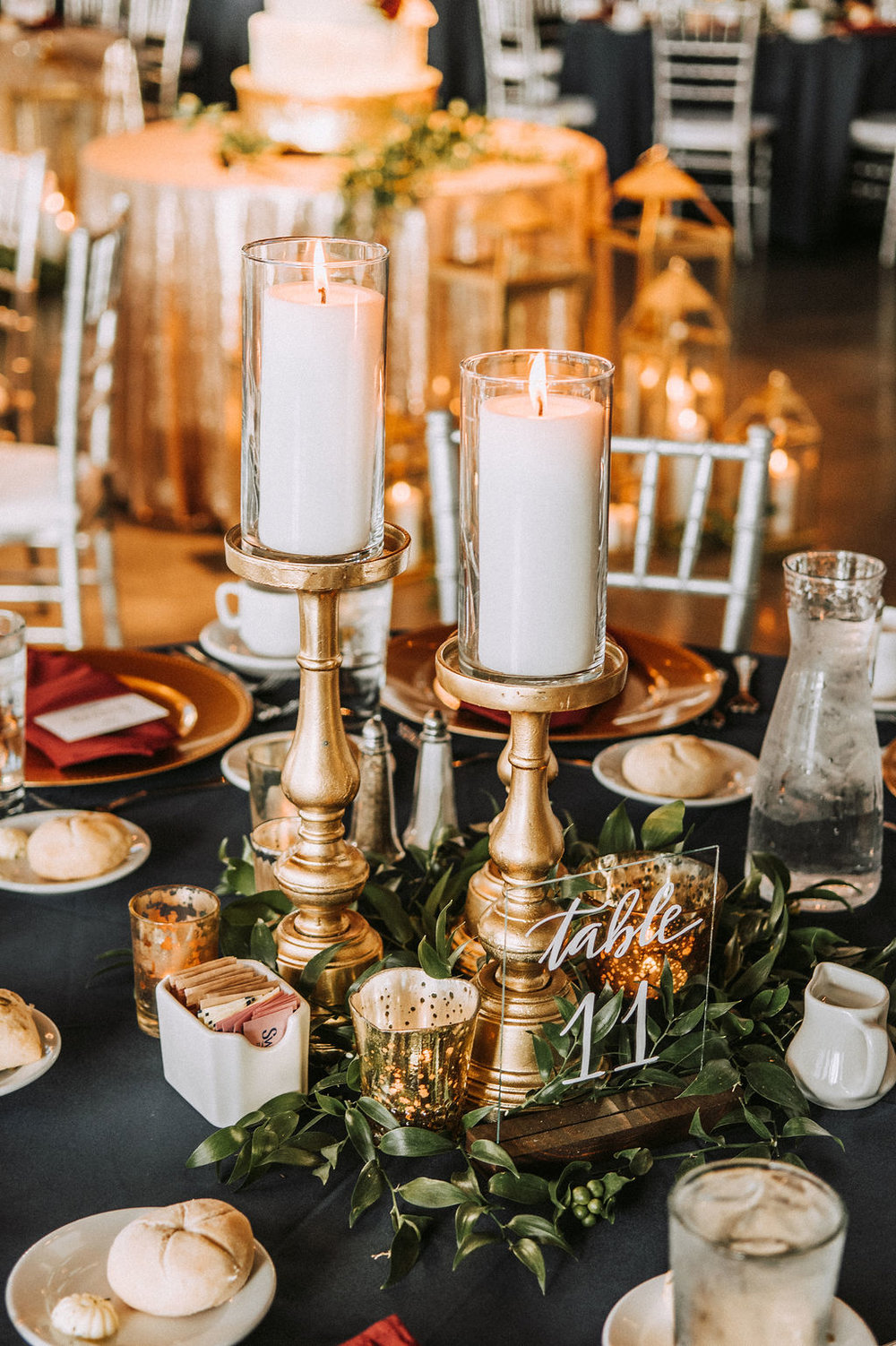 tall pillar candles on gold candle stick holders with glass table numbers and italian ruscus with mercury votives | Asher Marie Photography | Minneapolis day of coordinator | Muse wedding downtown.jpg