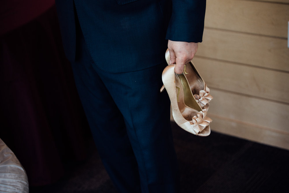 Dillinger Studios | Groom holding brides heels | 6 tips for  saving money on your wedding | Sixpence Events wedding blog Minnesota wedding planner
