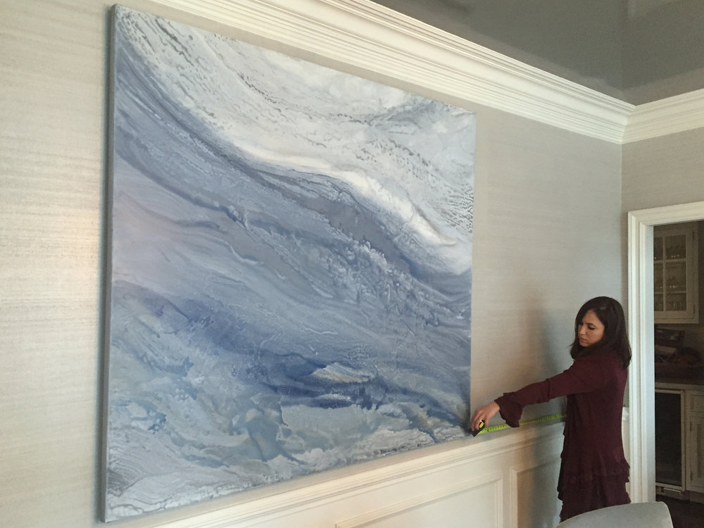 Director, Miranda Girard measures the final adjustments for an installed painting.