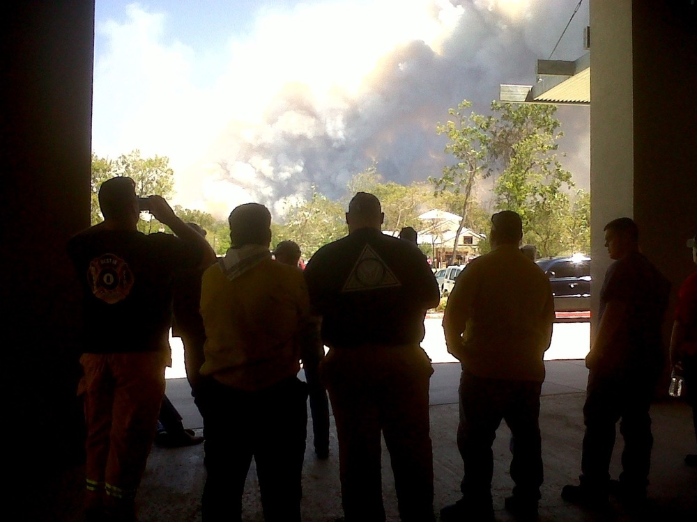 Firefighters take a break at the Bastrop County Convention Center on Labor Day in 2011 as smoke from the wildfire burning through thousands of acres fills the sky. Photo by Ciara O'Rourke.