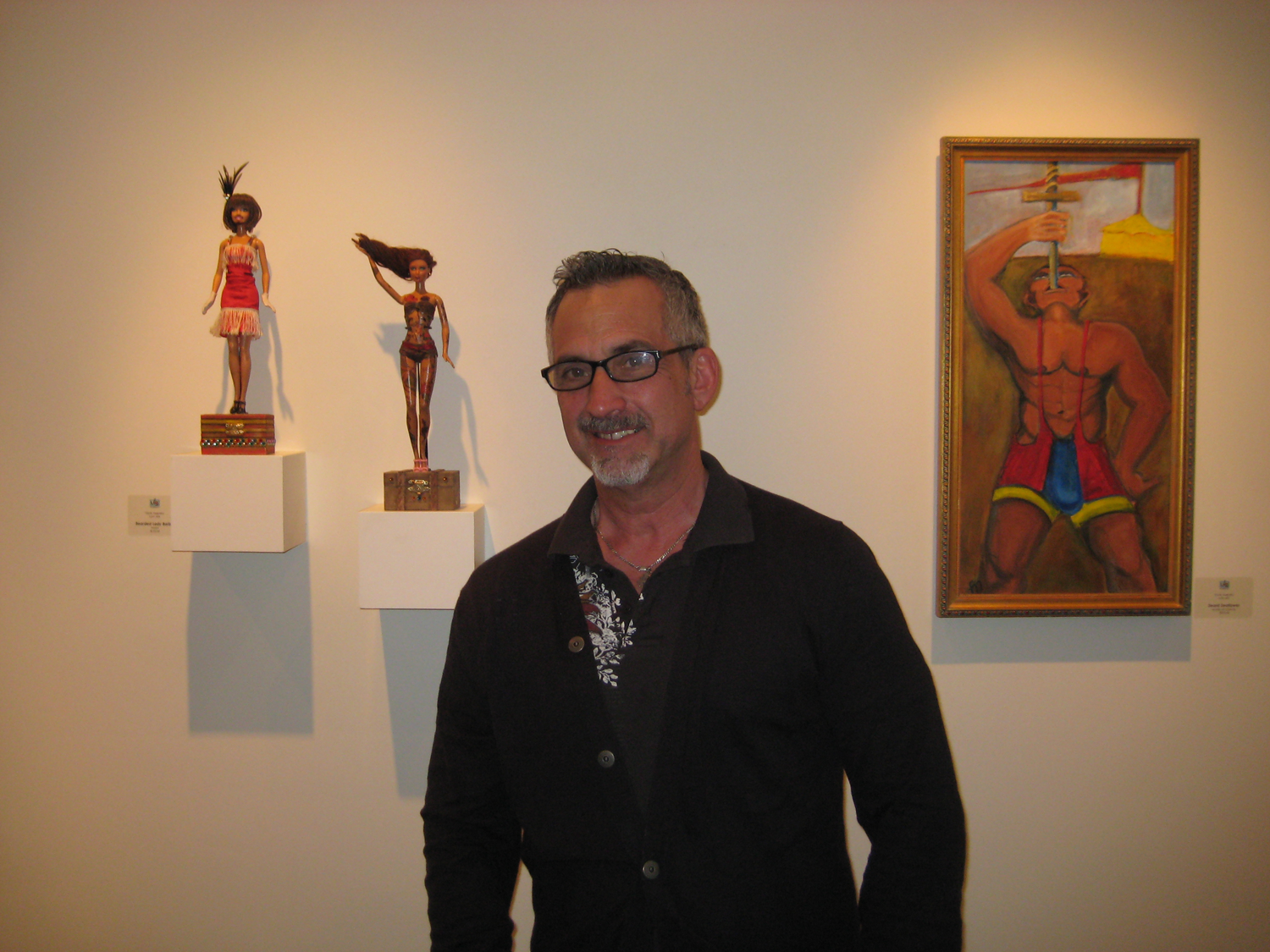 "Side Show Artist Frank Nagorka in front of his works, ""Bearded Lady"", ""Tattooed Woman"", and ""Sword Swallower"""