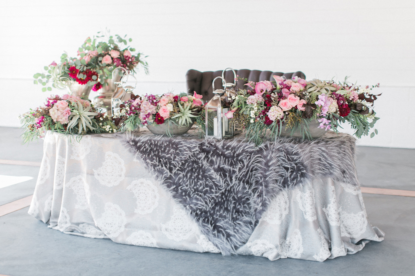 This table design is so unexpected! The gorgeous floral center pieces paired with fur over the luxe tablecloth is simply amazing.