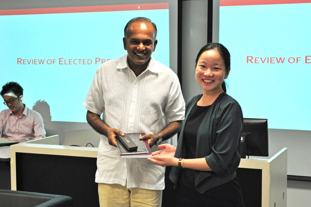 Ms Grace Teo, Deputy Chief Editor (Journal), presenting a token of appreciation to Minister Shanmugam.