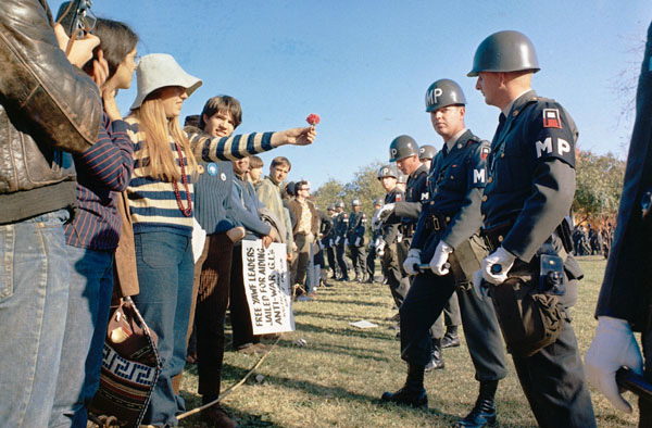 A female demonstrator offers a flower to military police on guard at the Pentagon during an anti-Vietnam demonstration, 1967, National Archives