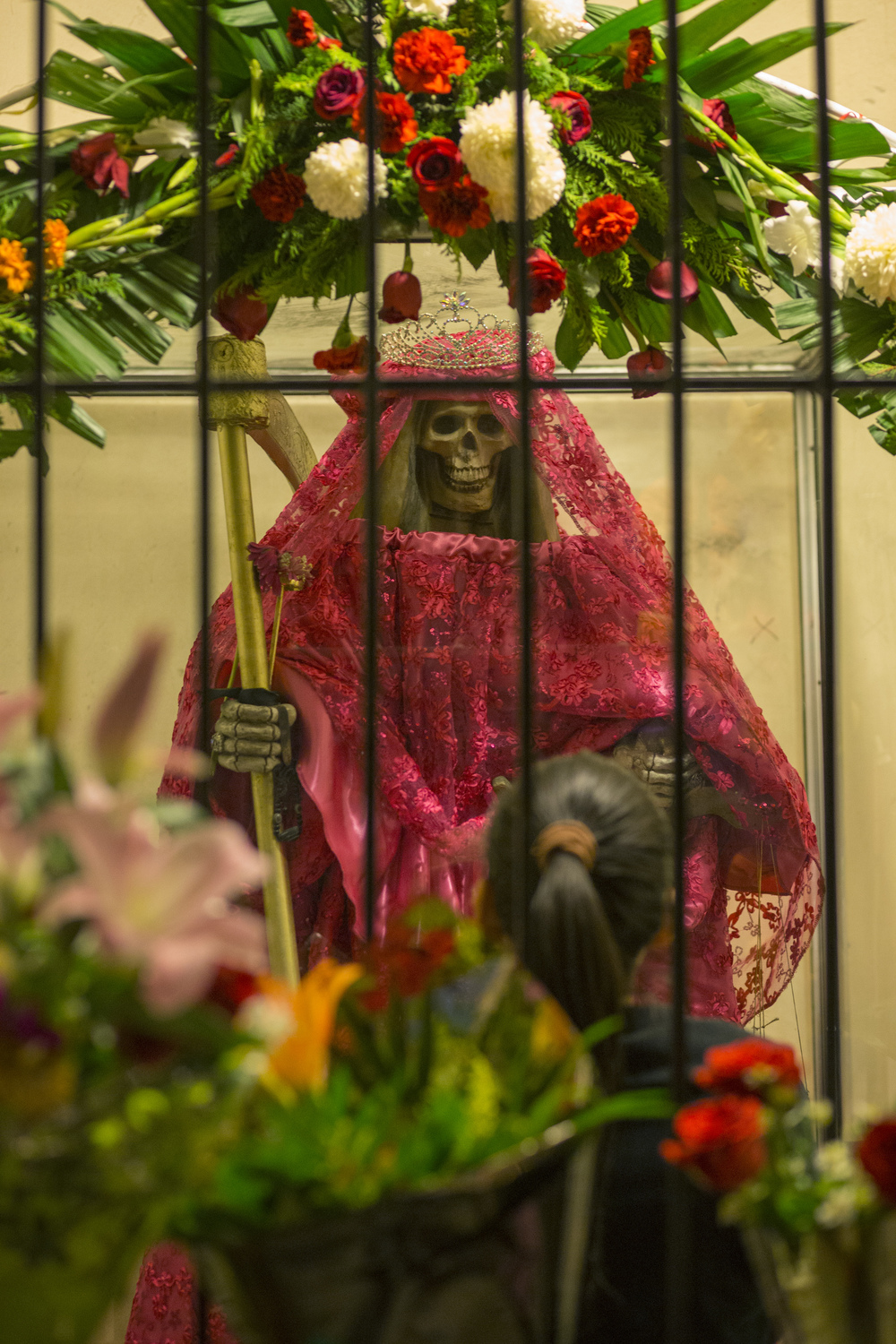 A woman prays at a Santa Muerte altar on Nov. 1, 2015 in a neighborhood on the outskirts of Tijuana. (Elaine Cromie)