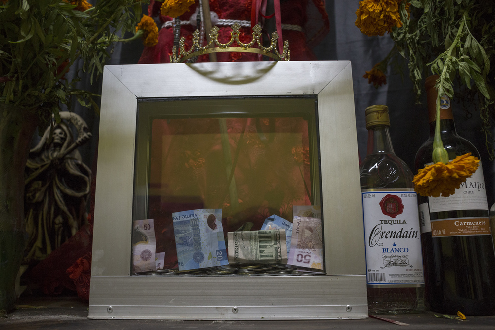 Visitors leave money as an offering at a Santa Muerte altar in Botanica La Chula, a store next to another altar and a gathering spot for Santa Muerte followers in Tijuana. (Elaine Cromie)