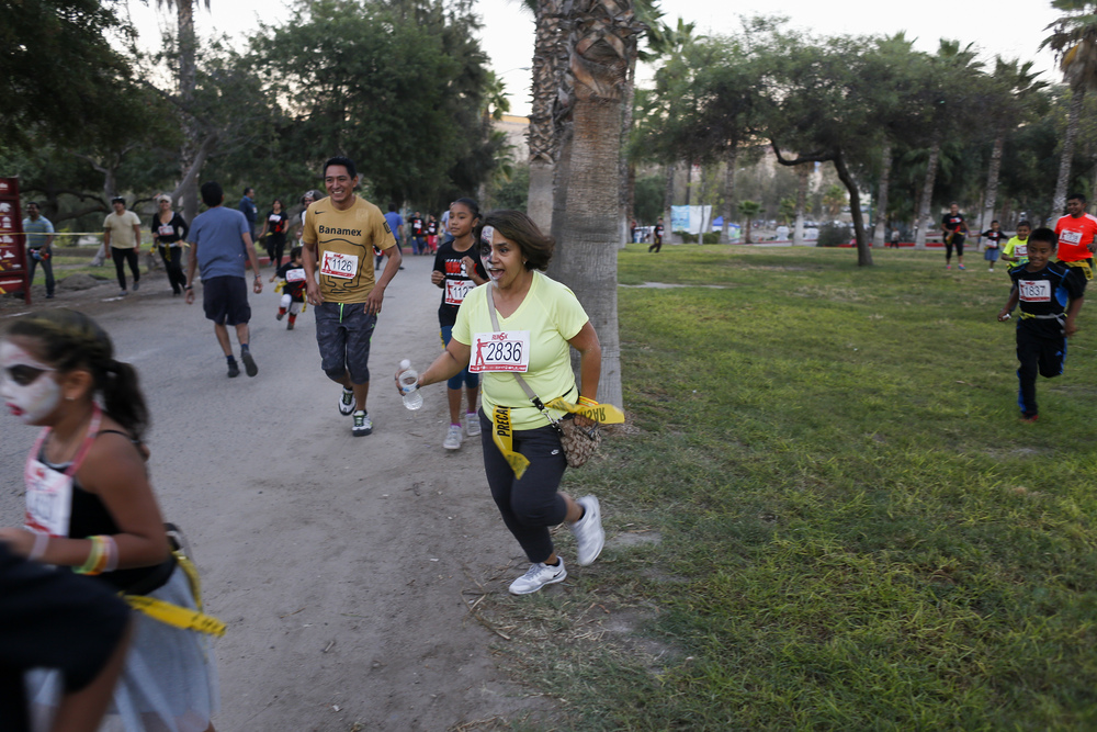 Participants of the Zombie Run 5K scurry through the course while trying to avoid volunteers dressed as zombies on Oct. 31, 2015 at Parque Morelos in Tijuana. (Elaine Cromie)