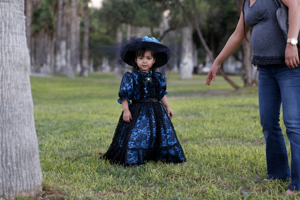 A young girl dressed as a Catrina Doll visits Parque Morelos with her family on Oct. 31, 2015 in Tijuana. (Elaine Cromie)