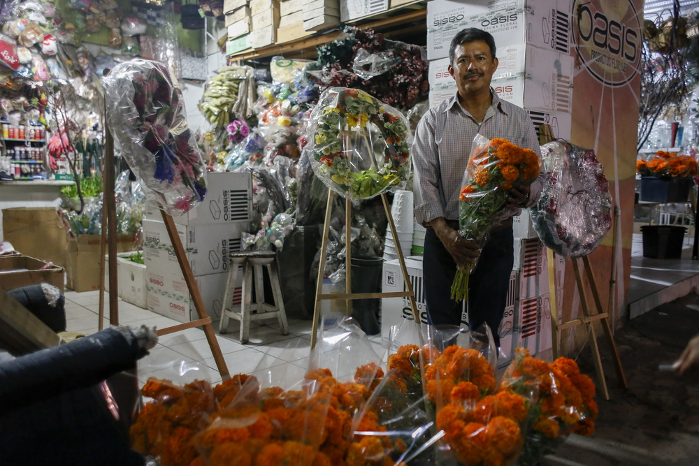 "Hugo Collado, a florist in Tijuana poses for a portrait outside of his flower shop on Oct. 31, 2015 in Tijuana. ""It's the combination of Dia De Los Muertos and Halloween. What happens is something magical, something different. But something beautiful,"" said Collado about the two holidays. (Elaine Cromie)"