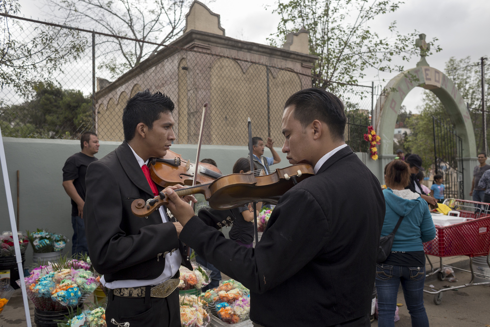 Two mariachis entertain the crowd outside of Pantéon Numero 1, Tijuana's largest cemetery on Nov. 2, 2015 also known as Dia De Los Muertos. (Elaine Cromie)