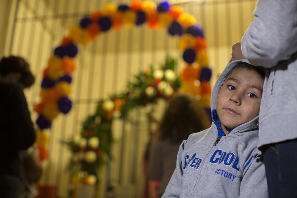 Byron stands with his family at a Santa Muerte altar on Nov. 1, 2015 in Tijuana as they pay tribute to his grandmother who passed away three months earlier. (Griselda San Martin)