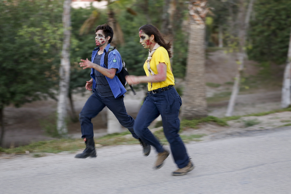 Volunteers dressed as zombies chase after adults and children participating in the Zombie Run 5K at Parque Morelos on Oct. 31, 2015 in Tijuana. (Elaine Cromie)